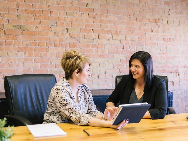Zwei Mitarbeiterinnnen unterhalten sich an einem Bürotisch mit einem Tablet