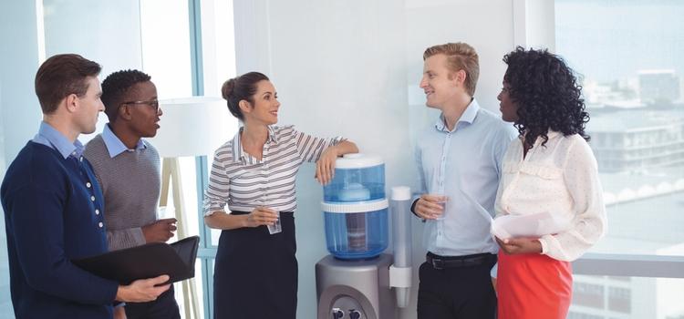 Mitarbeiter stehen um einen Wasserspender mit Gallone