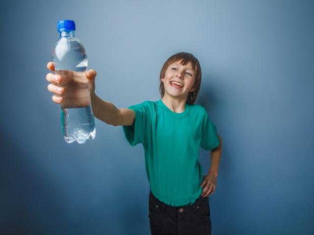 Junge mit einer Wasserflasche in der Hand