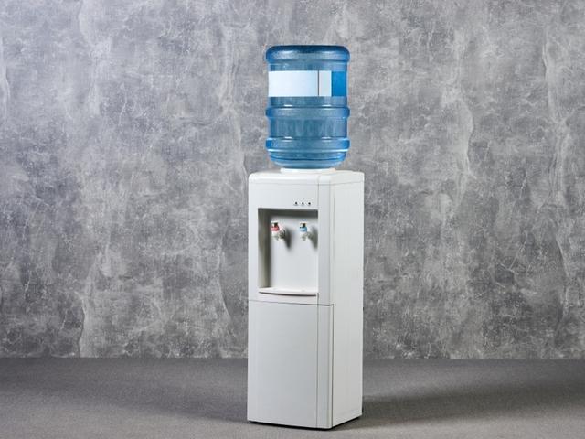 Wasserspender mit Gallone vor einem grauen Hintergrund
